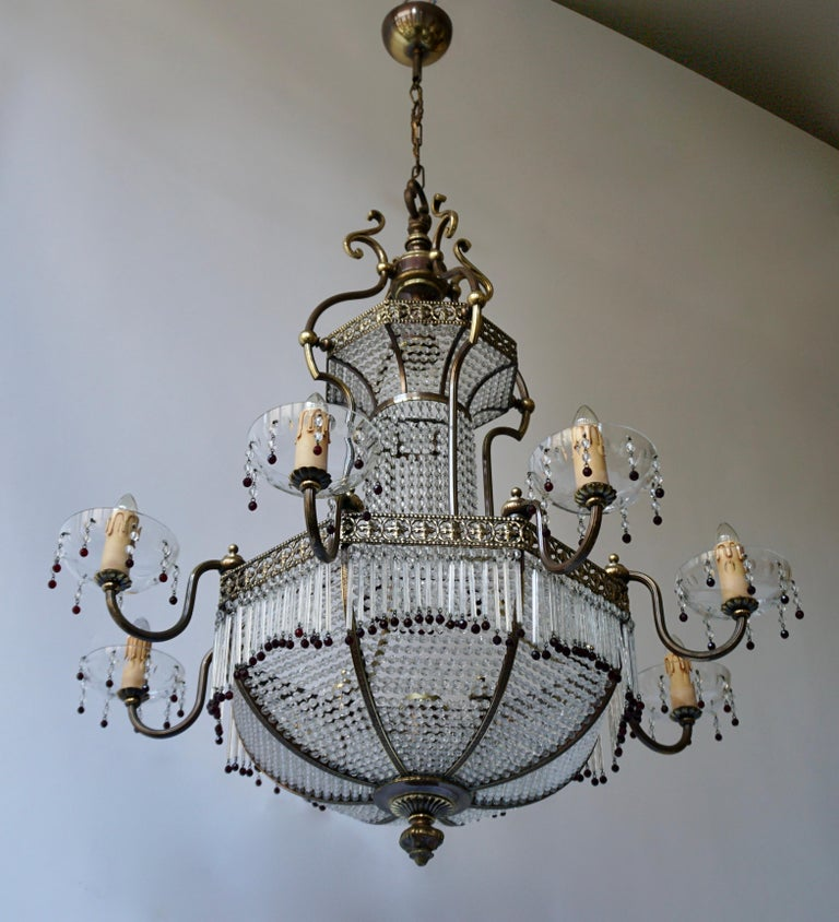 This beautiful French sac a perles chandelier has a copper wire mesh frame that is hung with hundreds of small glasses. The luster was made in Southern France circa 1950 and is in good condition. It has eight arms with candles on the outside and 2