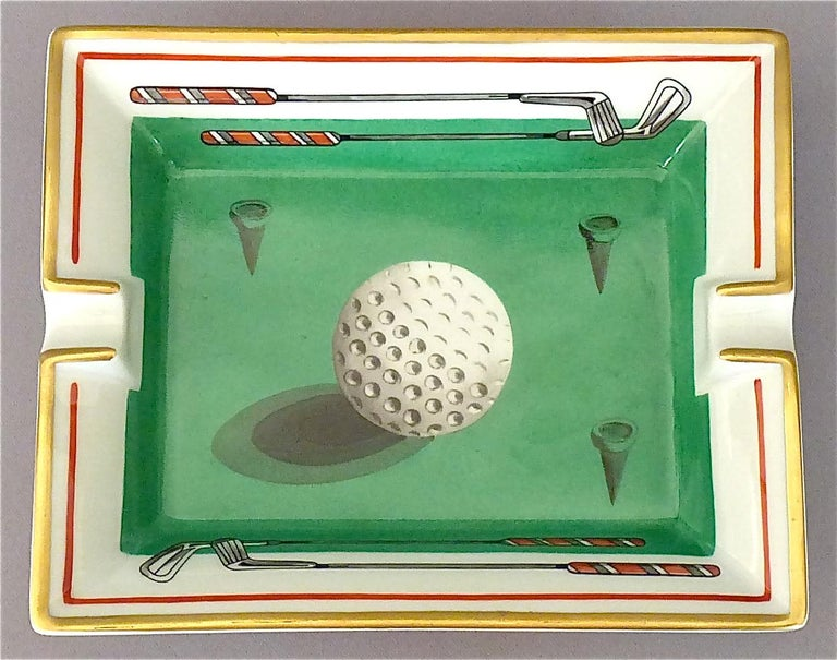 A fine and beautiful Hermès Limoges vintage oblong porcelain ashtray with golf ball motif in Fornasetti style, partly gilt, in colors green, white, grey and red. Marked Hermes Paris and Made in France to the side and suede covered to the base for