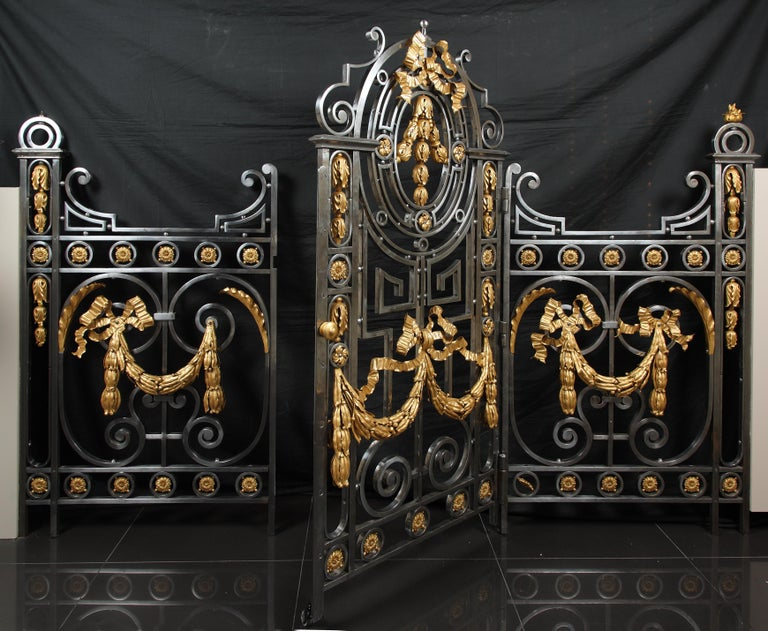 Made in polished wrought iron, interior gate composed of two gate-sides and an arched door, with an elegant decor made of scrolls, enriched with gilt bronze ornaments such as laurel garlands and tied ribbons.