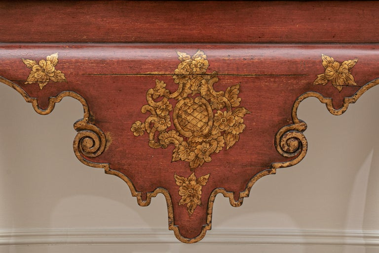 In a burgundy and gilt finish with an ebonized shaped top with gilt edge. Raised on tall cabriole legs with ball-and-claw feet. A large Venetian style shaped and carved apron in front with gilt floral cartouche (two intentional cracks for an antique