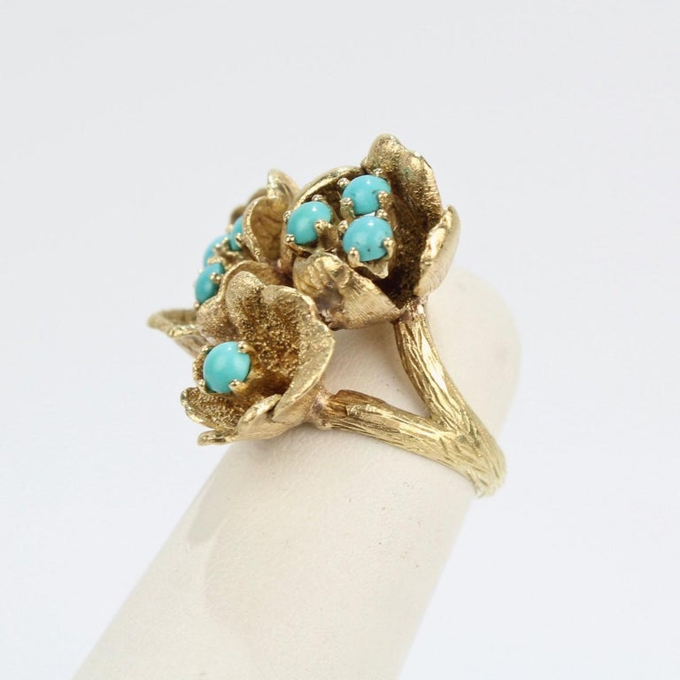 A fine J. Rossi 18K gold and turquoise ring with delicate gold flower blossoms.  The ring has textured gold that forms figural leaves, petals surrounding turquoise beads, and a 'twig' shank.   The posts holding the beads move just a little and allow