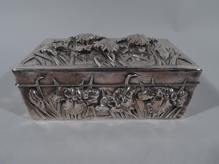 Turn-of-the-century Japanese silver box. Rectangular with hinged cover. Cover top and sides decorated with iris flowers set in eddying water. Ornament applied, chased, and engraved; ground hand hammered. Interior lined with stained wood; bottom