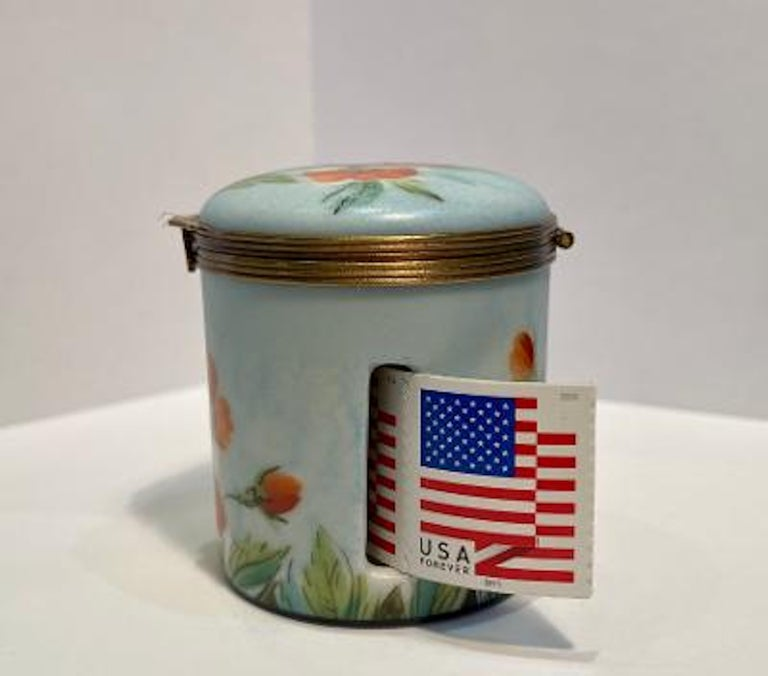 Fine quality and practical, Limoges porcelain cylinder shaped postage stamp distributer box is handmade and features a pretty pale sky blue background with skillfully hand painted budding and blooming orange poppies surrounding the entire circular