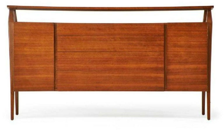 Fine MCM Gio Ponti figured walnut cabinet credenza having manufacturer label. Sleek and stylish lines with four center drawers flanked by two-side doors having fitted interiors.