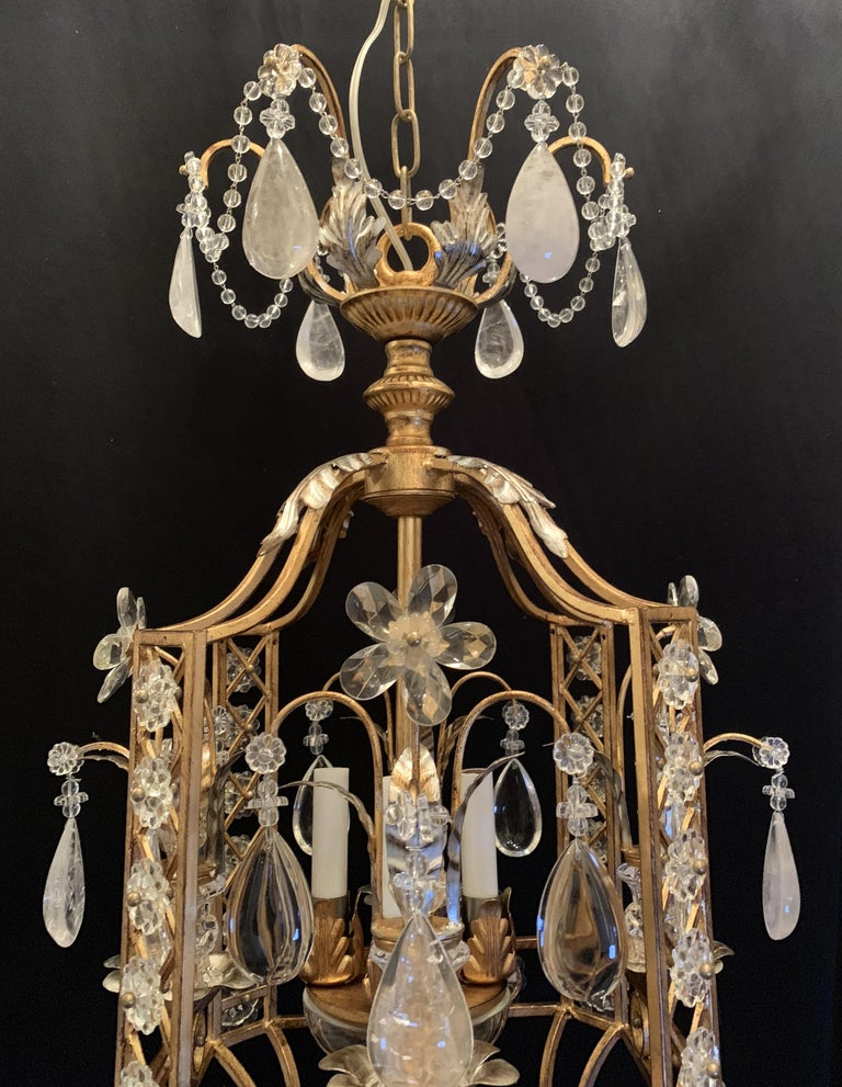 A fine Mid-Century Modern French Baguès style rock crystal 4 candelabrum light lantern pagoda form silver and gold gilt mix pair of chandeliers with beaded swags.  Each Sold Separately