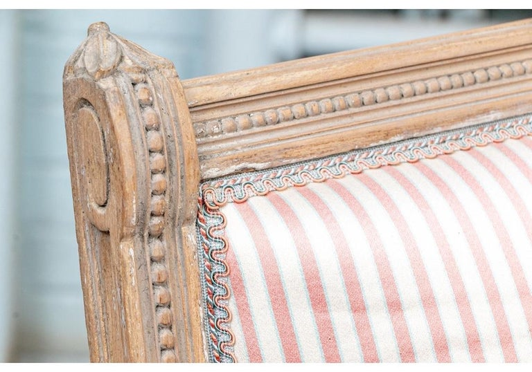 Very well constructed settees with carved frames in pale gray wash over natural wood, circa 1920s. With beaded crest rails and sloping arms with carved finials. The scrolled arm ends sloping into the fluted legs with carved leaves. With a beaded