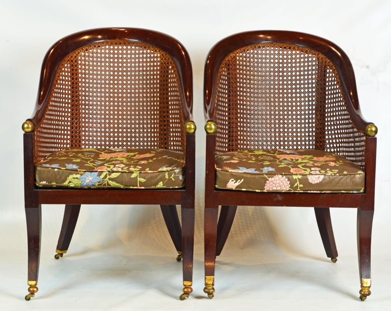 These chairs feature arm rests and back rails designed as continuous elegant curves joining the sabre style front legs by a brass ball. Back, sides and seat are mounted with woven cane and the rear legs continue in uprights to support the back rail