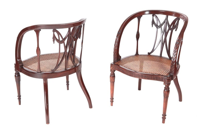 Fine pair of antique mahogany hepplewhite style library chairs, with attractive carved backs, lovely carved shaped arms, bergere seats, reeded serpentine front rail ,standing on fine carved turned legs to the front outswept back legs Lovely color