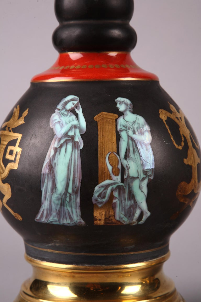 """Pair of Pompeian style gilded bronze-mounted black porcelain lamps. Necks and bodies finely decorated with antique figures and allegories painted in light blue """"grisaille"""" and gilded antique style motifs, such as braseros, pedestals and vases."""