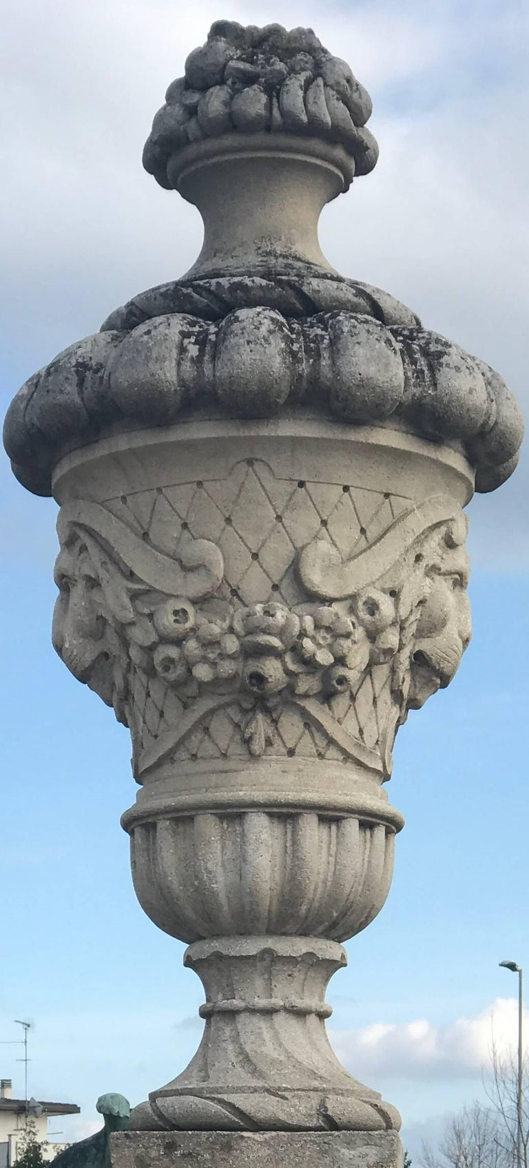 Finely carved elegant vases with lion mascarons and flower garlands.