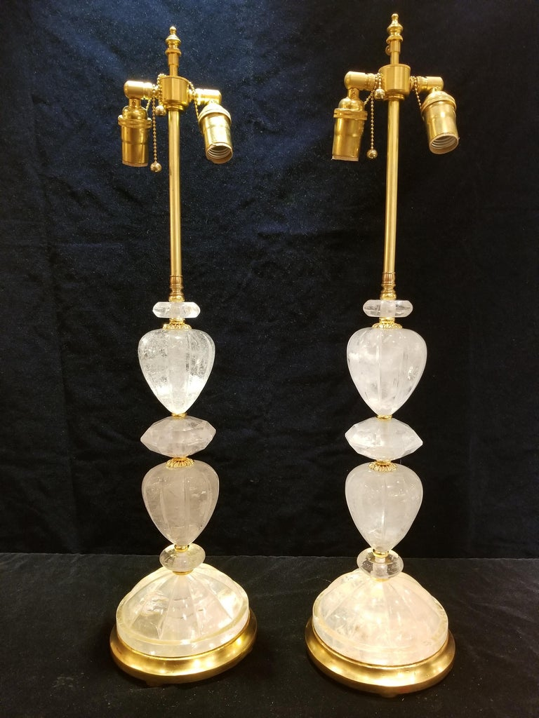 A Fine Pair of French Louis XVI Style Hand-Carved Rock Crystal Ormolu and Gilt wood Lamps. This illustrious pair of Louis XVI style hand-carved rock crystal and ormolu lamps are exceptionally designed and hand-crafted. Each section of the rock