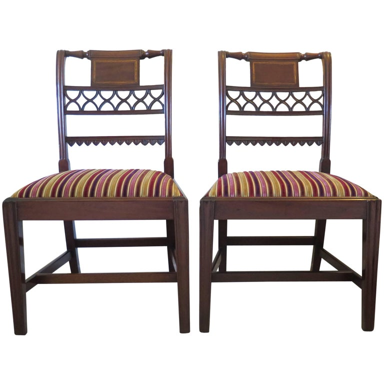 These are a fine and elegant pair of English mahogany side / dining chairs from the English Sheraton Period of George III, circa 1790 and with beautifully carved detail.  The chairs have square backs with flute moulded sides and have intricate