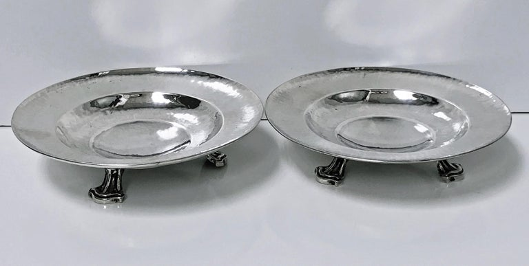 Fine pair of Omar Ramsden Sterling Silver dishes, London, 1931. Each on three stylised turned supports, welled interiors, planished hammered silver. Marks on each for Made by Omar Ramsden, London in 1931 and Omar Ramsden Me Fecit. (Latin: Omar