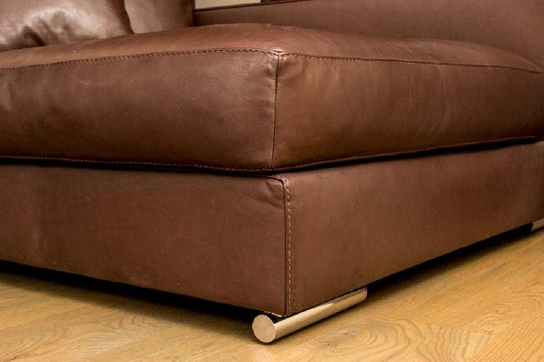 Contemporary large scale brown leather lounge by Rivolta, Italy, dark brown leather with fine stitching and toss pillow. Mounted on cylindrical metal feet.  Condition: Gently used condition with light signs of use.