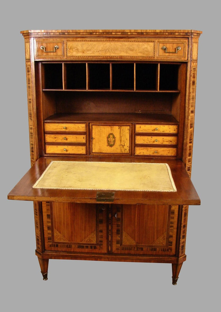 A fine quality Dutch or Northern European neoclassical style inlaid tulipwood, satinwood and specimen wood secretaire abattant, the counterweighted drop front opens to reveal a fitted interior, the prospect door inlaid with three ostrich feathers