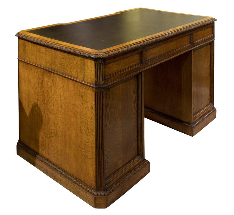 A very fine quality oak pedestal desk. The top moulding carved with rosettes; above nine drawers flanked by canted, stop fluted corners and dentilled plinth carving, panelled to the rear, cedar drawer linings & 'aesthetic' brasses attributable to