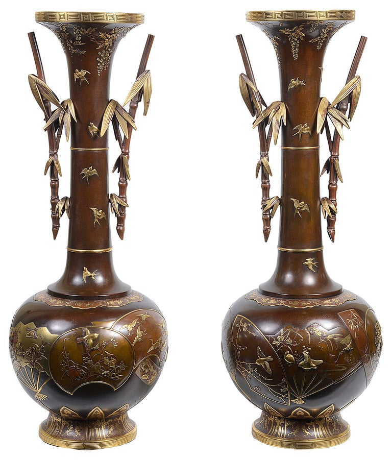 A beautiful fine quality pair of Japanese Meiji period (1868-1912) Miyao bronze and gilt vases, each having classical motif decoration, swifts flying around the necks, faux bamboo handles, the bulbous bodies having fan shaped panels depicting flying
