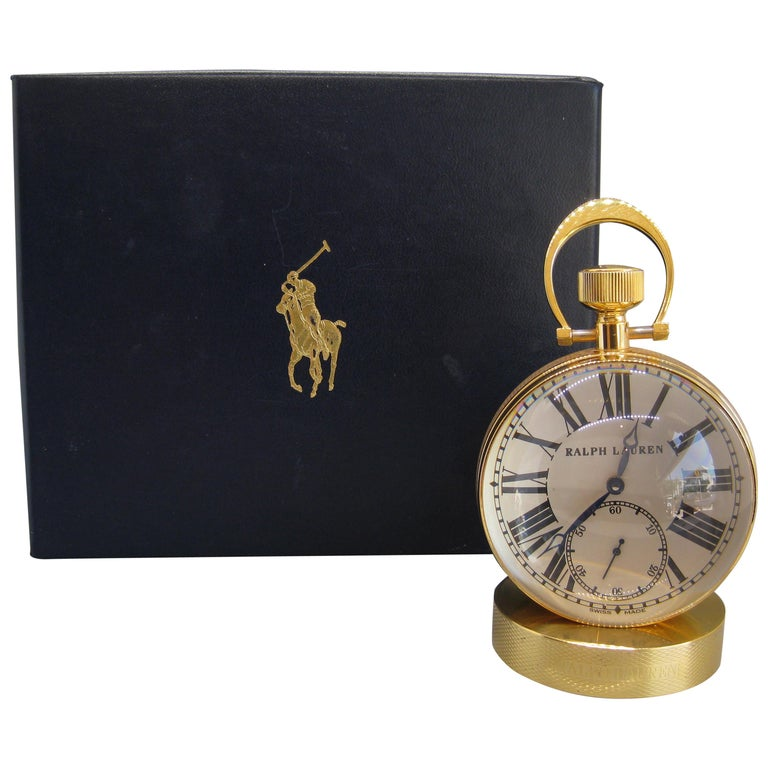 Fine Ralph Lauren brass and glass ball shaped desk clock. The clock works and keeps accurate time. Has Swiss 17 jewel works. Comes with the original box. Great design and form. Comes with the solid brass base to hold the clock. In excellent shape