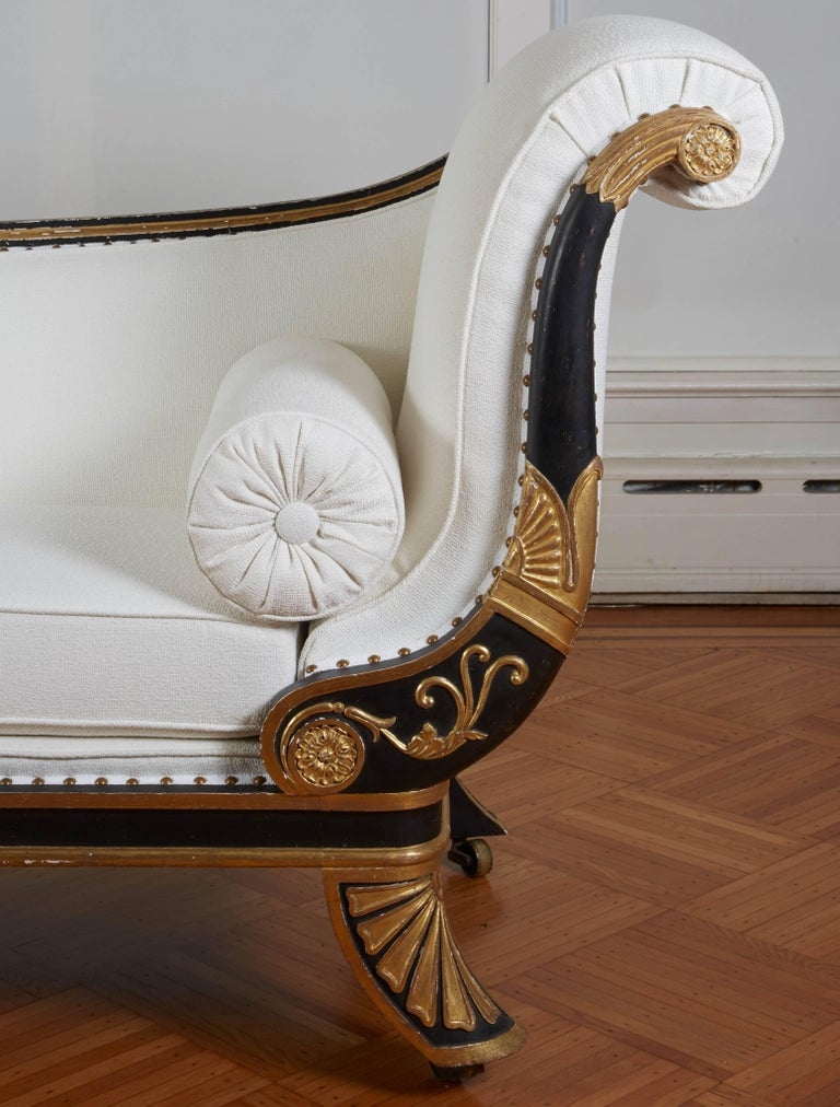This daybed stands out for its impressive scale. With outward scrolling upholstered side and downswept back within an ebonized surround with gilt acanthus and lotus leaf decoration; the seat over a gilt-banded rail supported on outswept feet with