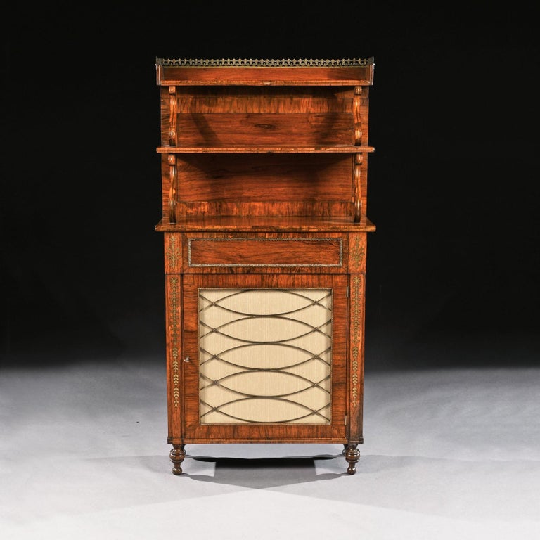 A fine quality Regency antique rosewood and brass inlaid chiffonier of diminutive proportions with waterfall superstructure.  English, circa 1810-1815.  This fine quality Regency chiffonier decorated with brass inlay has a two tier upstand