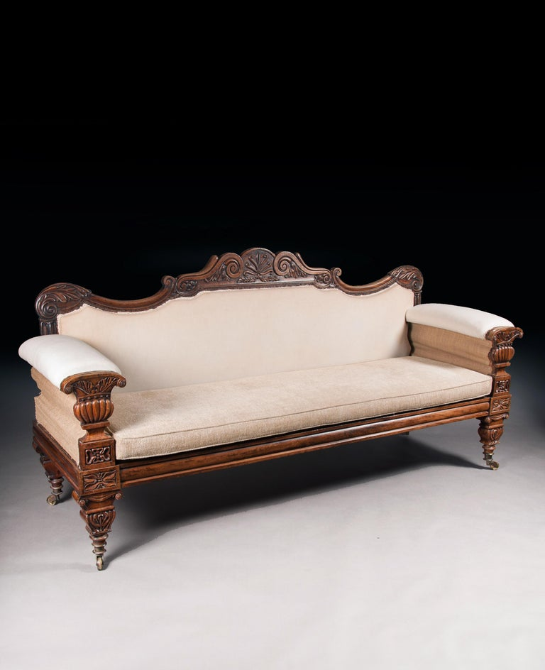 A very fine English Regency carved mahogany sofa after a design by John Taylor incorporating Greek and Roman elements.  English, circa 1825.  Having acanthus leaf wrapped carved scroll ends, the top rail features a shaped foliate double scroll