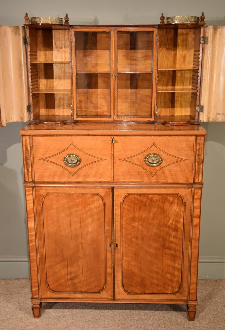 An early 19th century Secretaire cabinet in the manner of George Oakley, the upper gilt metal gallery over a pair of glazed cabinet doors flanked by barrel form cabinet doors enclosing adjustable shelves. The Secretaire cabinet is fitted with solid