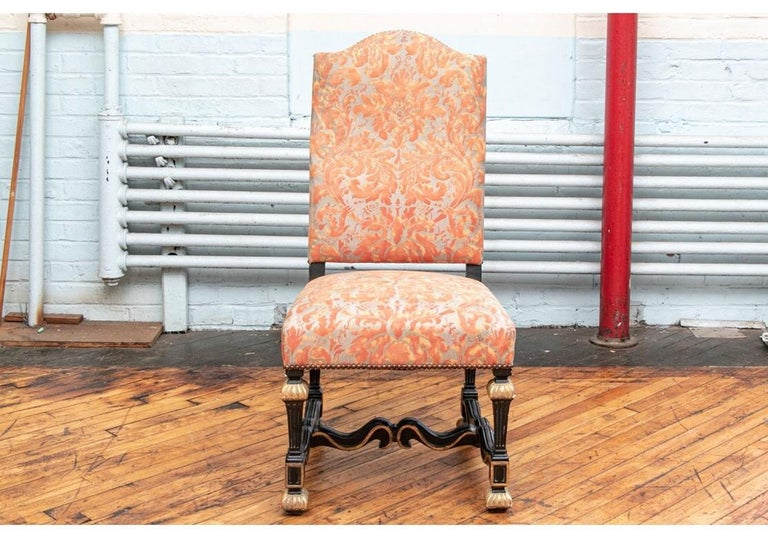 A superb set of 12 Louis XVI style dining chairs with high shaped backs having a carved and ebonized frames and legs. Fluted tapering legs with gilt tops and feet and fine scrolled H-stretchers. Upholstered on the front and seats in a coral/gray