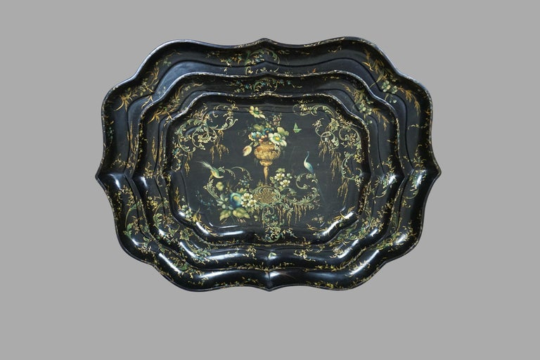 A rare set of 3 English gilt and paint decorated papier mâché scallop form trays with foliate and bird decoration on a black field, the central floral bouquets flanked by exotic birds. It is unusual to find complete sets of graduated trays of this