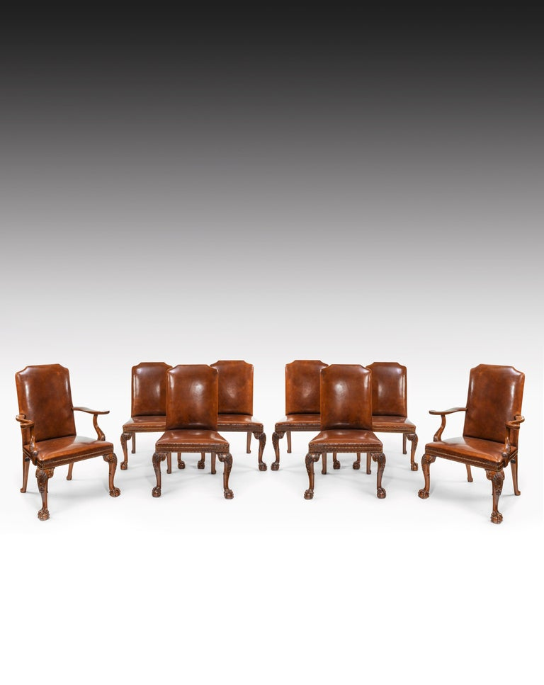 A fine quality set of eight carved walnut cabriole legged leather upholstered dining chairs, in the Queen Anne style, consisting of two carvers and six single chairs.  English, circa 1910.   Of generous proportions, the rectangular shaped