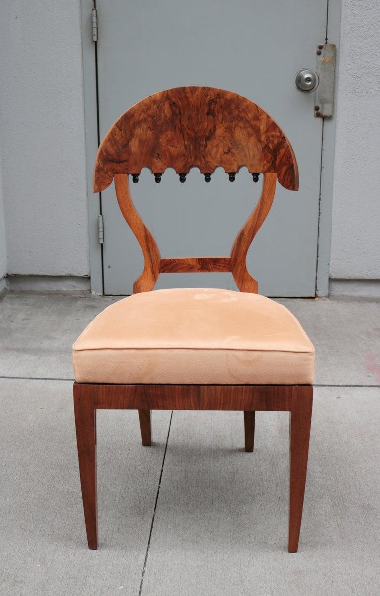 A fine set of four Biedermeier side chairs. Walnut burl with ebonized details.