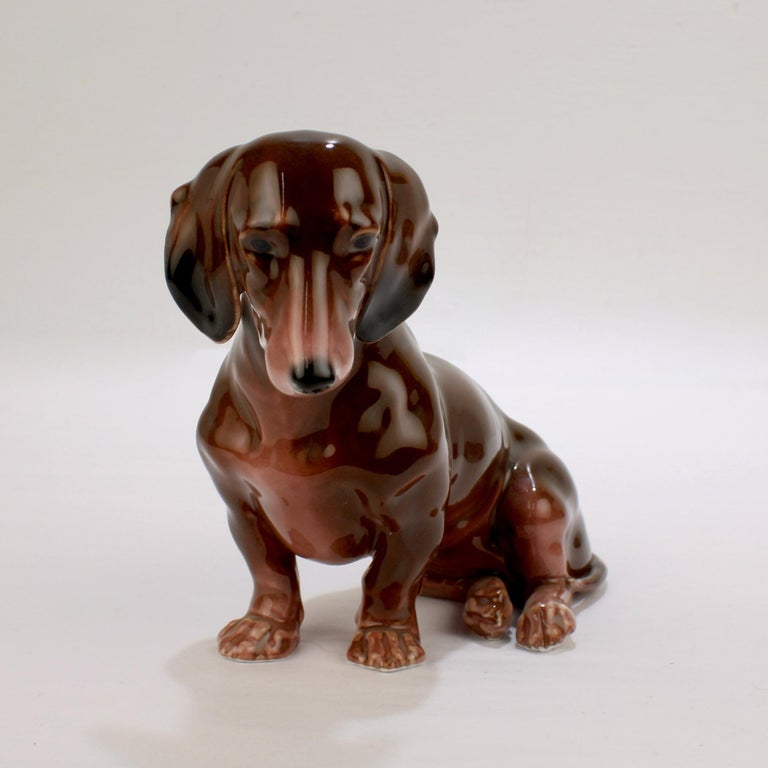 Offered here for your consideration is a wonderful Karl Ens porcelain figurine.  Modeled as a seated Dachshund dog.   Decorated principally in brown tones with black and white features.   Model no. 2578.  The Karl Ens factory was a