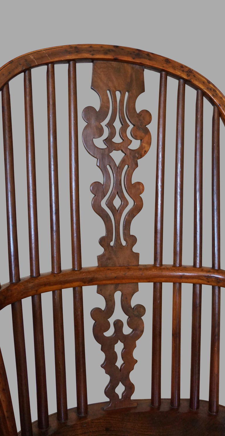 An excellent quality English yew wood narrow arm Windsor chair, the elaborate wavy pierced back splat over an elm saddle seat, supported on turned legs connected with crinoline stretcher. Lovely honey color with good patina. The back splat is