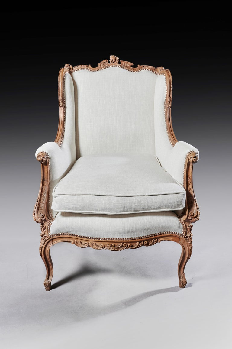 A finely carved 19th century French Louis XV style wingback armchair upholstered in linen.  French, circa 1870.  A decorative and well carved solid walnut wing back armchair having a shaped back with winged show wood sides falling to scrolled
