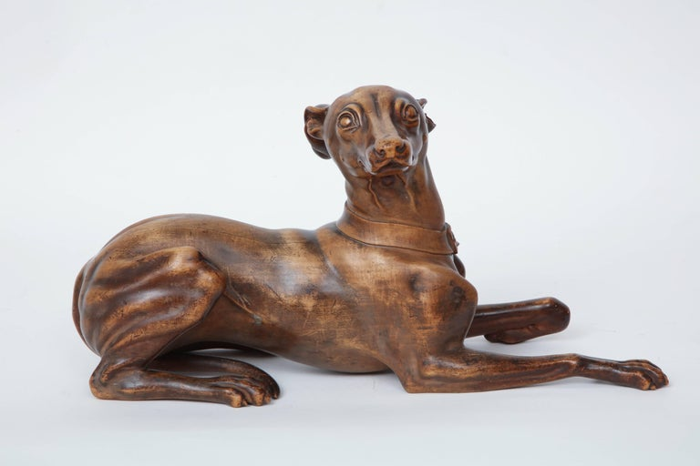 A finely carved fruitwood or beechwood recumbent whippet, probably English, circa 1900s. Carved in an extremely realistic manner with a very fluid hand. Good color and patina with a wax finish.