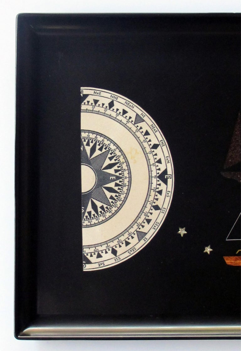 A finely crafted and hand-inlaid American midcentury black resin tray by Couroc of Monterey; this charming tray centering inlaid sailboats flanked by a compass and compass rose; all hand-inlaid by master craftsmen; Couroc began in 1948 in Monterey,
