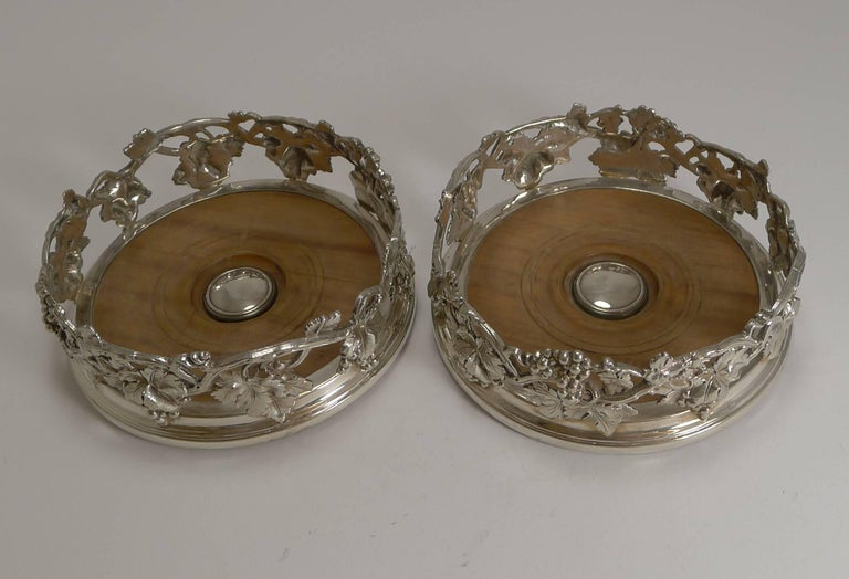 A magnificent set of early Victorian Elkington silver plate wine coasters, with an attractive cast grape vine design with lovely detail. The coasters have turned wooden bases, with a central silver plate boss without engraving.  Both coasters