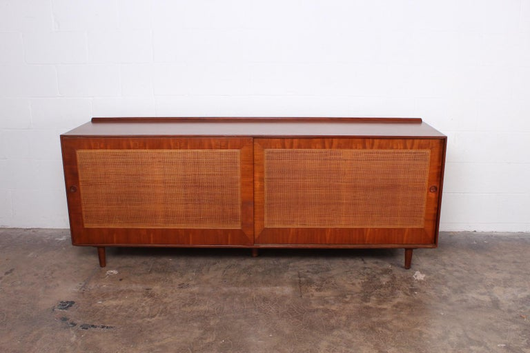 A walnut sliding door cabinet with cane fronts. Designed by Finn Juhl for Baker.