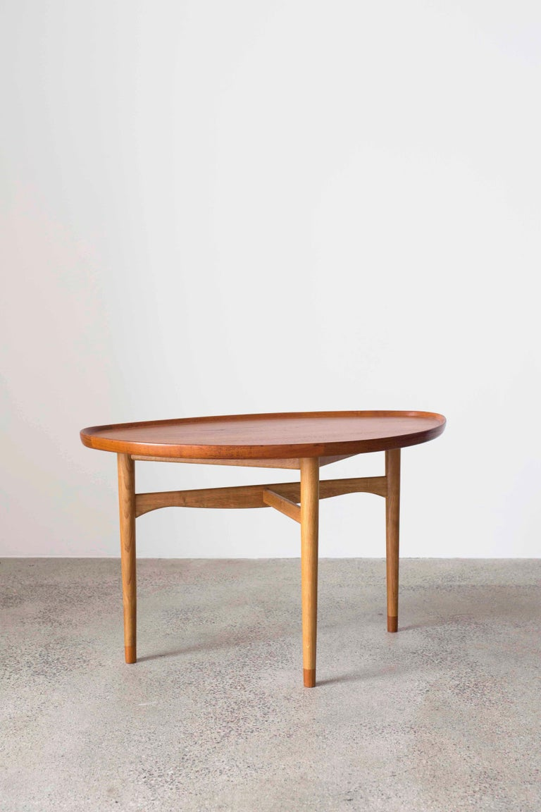 Finn Juhl coffee table. Tabletop with raised edges and leg ends of teak, frame of oak.