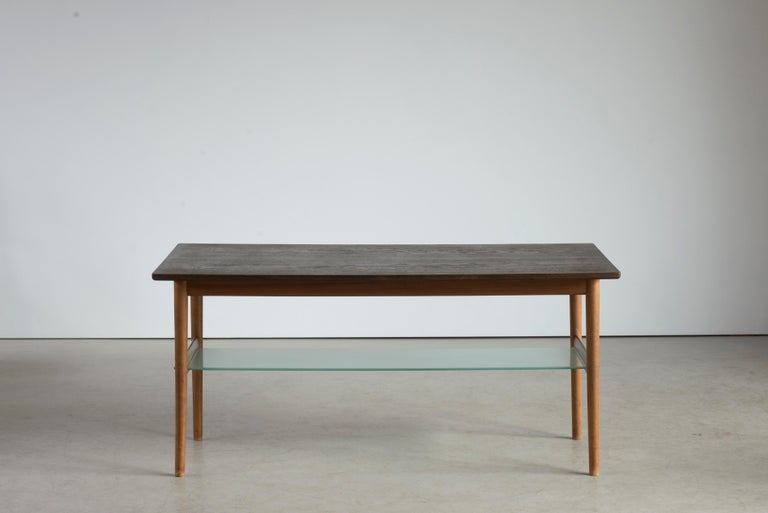 Coffee table with walnut frame, rectangular top of marsh oak. Executed by cabinetmaker Niels Vodder, 1955. Stamped by maker. Measures: H. 60 cm., L. 129.5 cm., W. 65 cm.  Acquired at the Copenhagen cabinetmakers' guild exhibition in