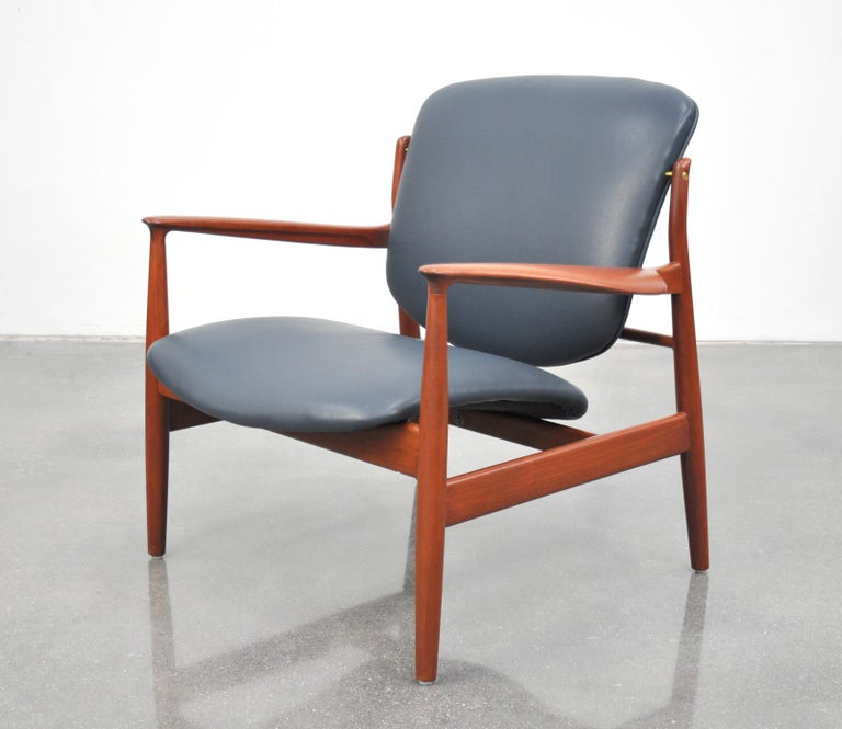 An iconic midcentury Danish modern FD136 easy chair designed by Finn Juhl for France and Daverkosen (later named France and Son) in the 1950s. The seat and backrest have been reupholstered in a gorgeous dark blue pebbled leather. The splendidly