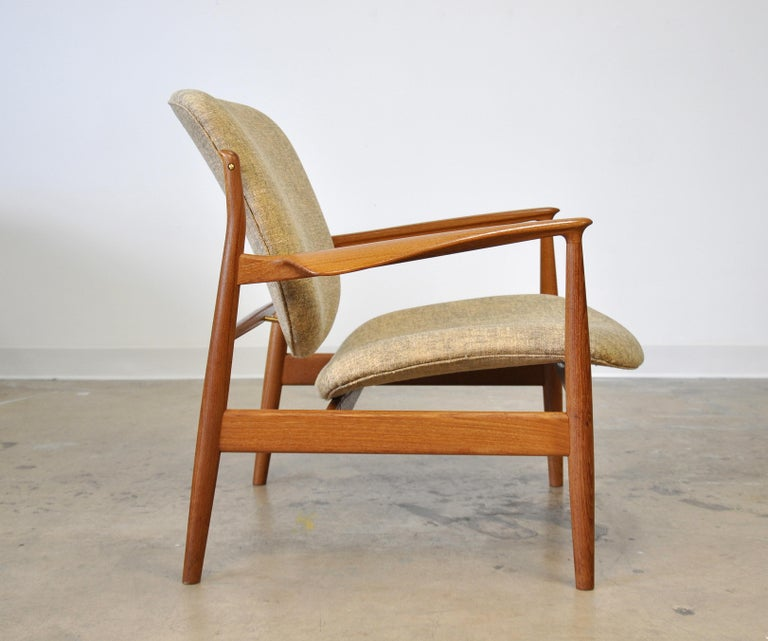 Iconic midcentury FD136 vintage easy chair designed by Finn Juhl for France and Daverkosen (later renamed France and Son) dating from the 1950s. The splendidly sculpted teak open frame and the floating seat and back of this armchair make for truly