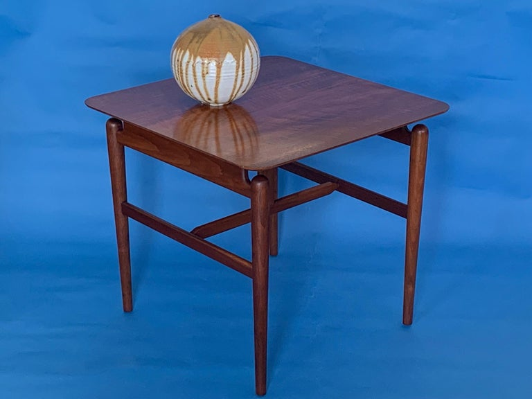A classic occasional or lamp table designed by Finn Juhl and produced by Baker, circa 1950s. Beautiful American walnut with hand polished, floating top. Finely crafted in the great Baker Furniture tradition.