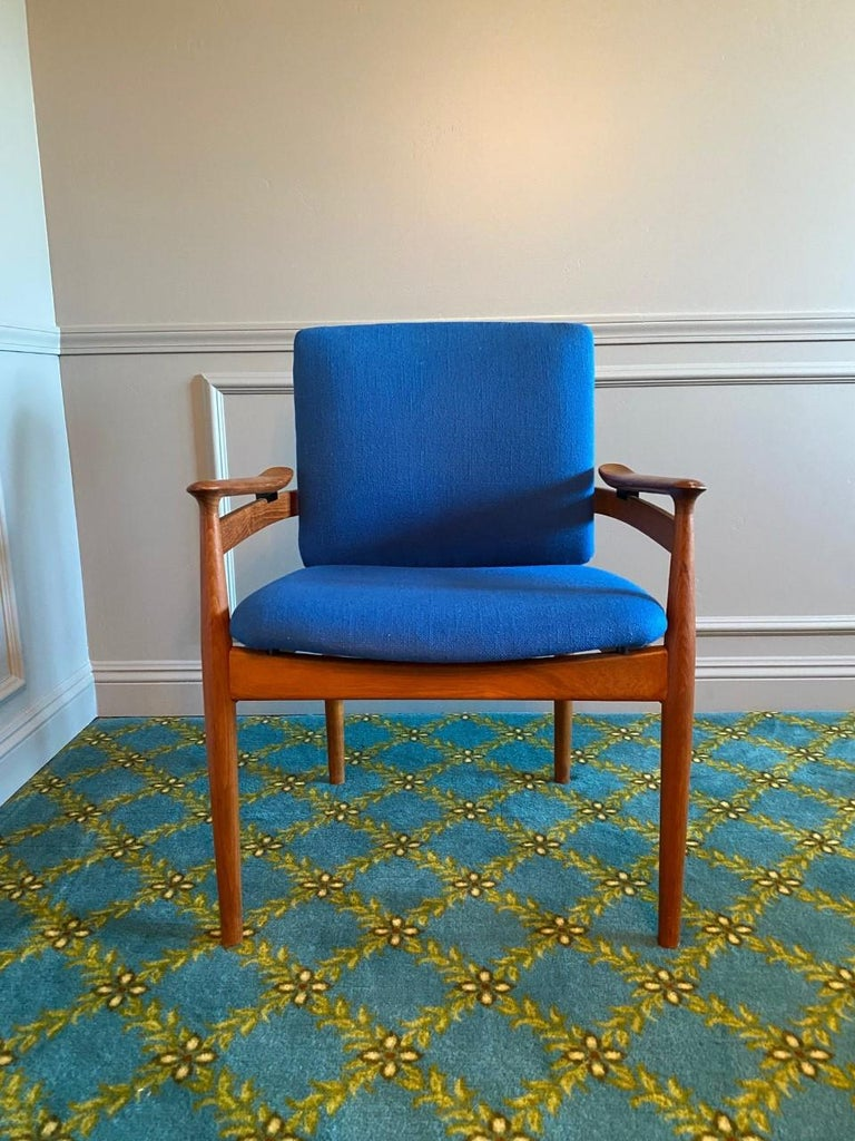 Designed by Finn Juhl for France & Son and imported by John Stuart, this handsome set of chairs features generous and comfortable seats that float within teak frames. They are upholstered in an original beautiful blue boucle fabric. In great