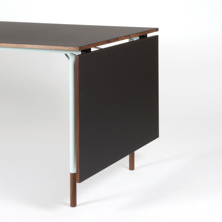Nyhavn dining table designed by Finn Jhul Manufactured by One collection Finn Juhl (Denmark) Light blue metal structure, black linoleum and walnut wood.  Several of Finn Juhl's simple and beautiful designs from the 1950s are combined with color
