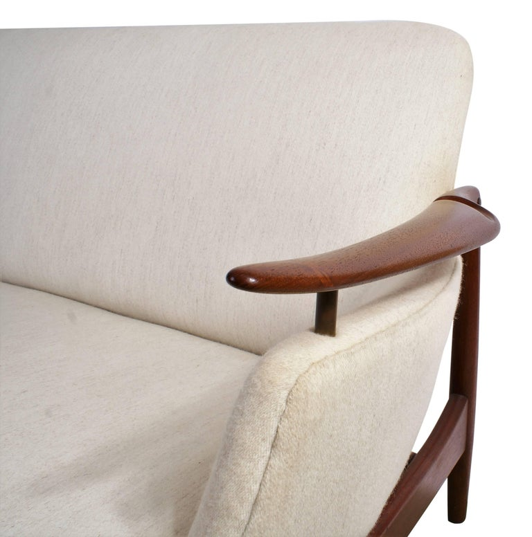 Finn Juhl NV53 three-seat sofa in teak and fabric for master cabinetmaker Niels Vodder. Sofa has been re-upholstered in Savak fabric (fabric designed by Tove Kindt-Larsen) and is finished with nails under the seat. It is very unusual to see this