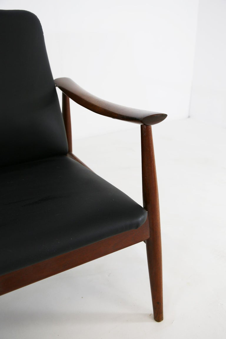 Finn Juhl for France & Son rare model 138 sofa with teak frame and elegantly curved arms, seat and back newly upholstered in black leather, Denmark, late 1950s. Applied manufacturer's label on frame. Ships from our Milan warehouse and we offer