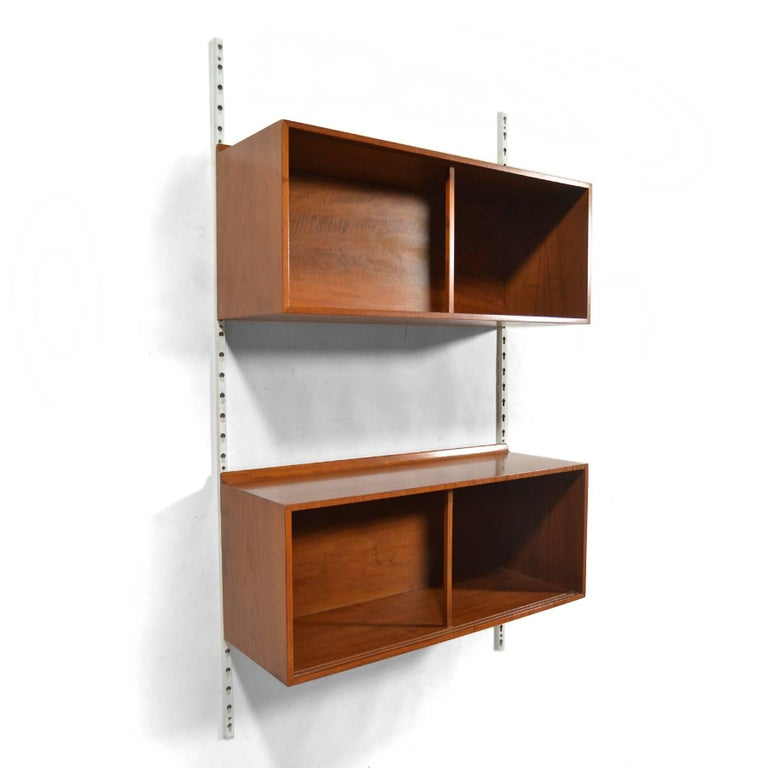 This pair of walnut Finn Juhl wall-mounted cases mount on metal uprights and can be adjusted and configured as desired. They feature details that many of Juhl's designs for Baker Furniture share, including the raised lip on the back edge.