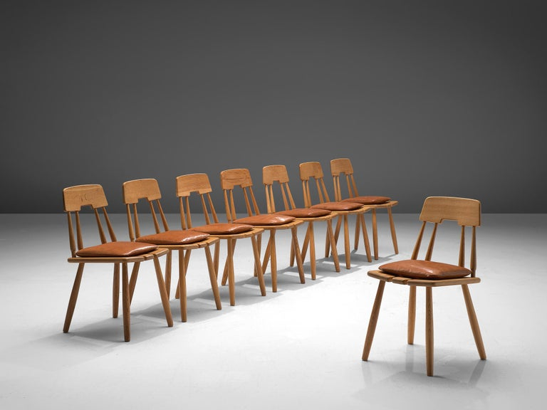 Set of eight dining chairs, oak, leather, Finland, 1950s  This set of eight chairs in solid oak features elegant details in the backrest. Here four cylindrical bars with one horizontal part form the back. The seating consists of three slats and