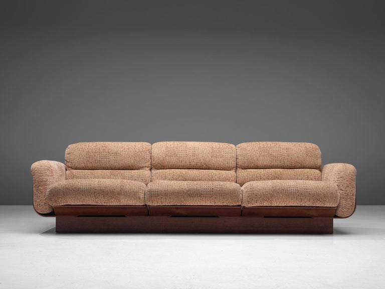 Asko, three-seat sofa, teak and upholstery, Finland, 1960s  Bulky three-seat basket sofa in teak that functions as the shell that keeps cushions in their position. The base is solid and gives the appearance of a seat that flows. The loose cushions