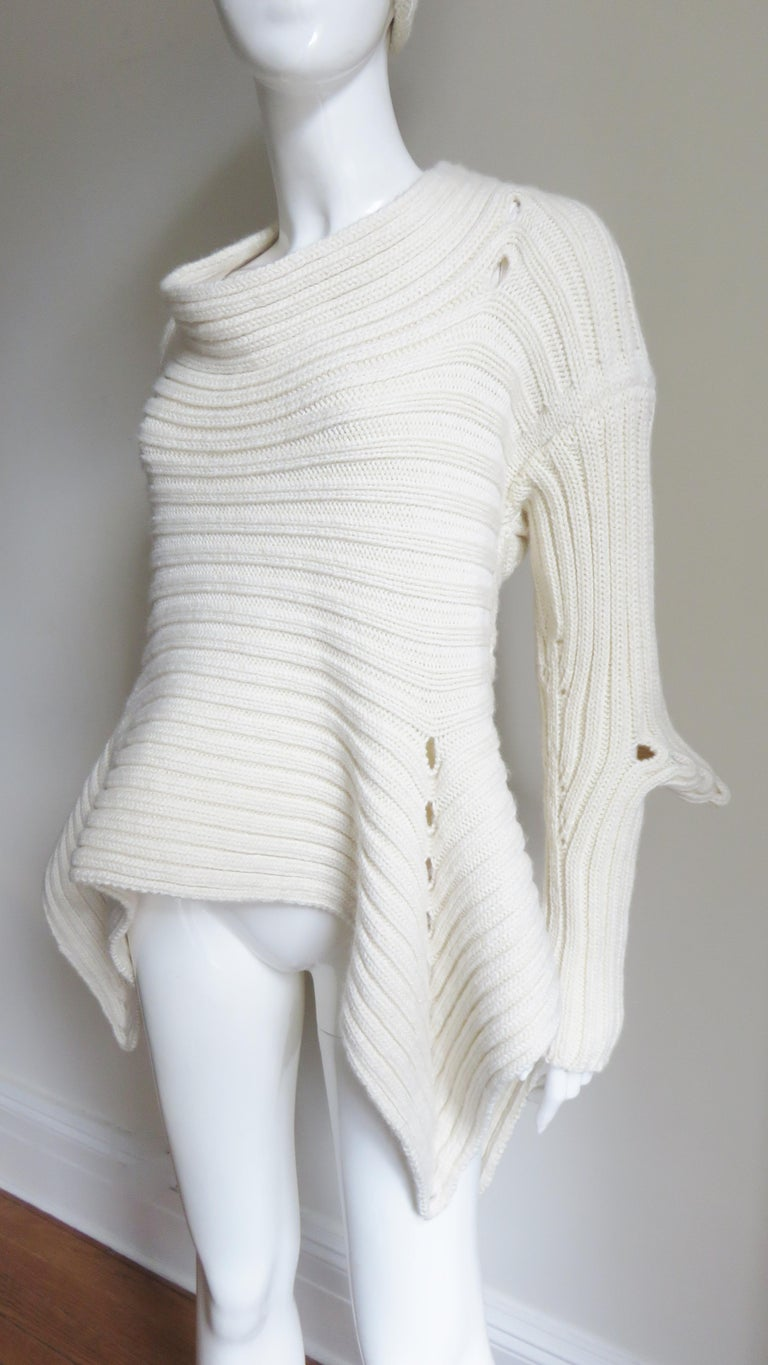 A fabulous off white wool Irish hand knit sweater and hat by Fintan Mulholland.  It is unique with a pointed hem and elbows with rows of holes along each and across the upper back.  It comes with a matching hat. Fits sizes Small, Medium,